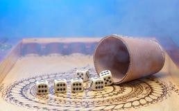 Elemente des Spielens auf einem geschnitzten hölzernen Brett Abbildung sechs, blauen Hintergrund und Rauch Stockfotos