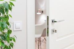 Elementi del primo piano dell'interno dell'appartamento Porta bianca socchiusa immagini stock