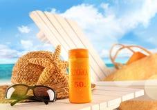 Elementi della lozione e della spiaggia di Sunblock sulla tabella fotografia stock libera da diritti