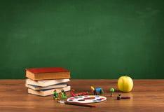 Elementi della scuola sullo scrittorio con la lavagna vuota Immagini Stock