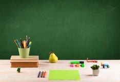 Elementi della scuola sullo scrittorio con la lavagna vuota Immagine Stock Libera da Diritti