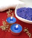 Elementi essenziali della stazione termale (sale, tovaglioli, candela e fiore blu) Fotografie Stock