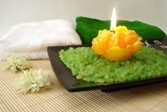 Elementi essenziali della stazione termale (sale, tovaglioli, candela e fiore verdi) Immagine Stock