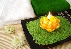 Elementi essenziali della stazione termale (sale, tovaglioli, candela e fiore verdi) Immagini Stock
