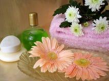 Elementi essenziali della stazione termale (sapone, bottiglia di sciampo e tovagliolo con i fiori) Fotografie Stock