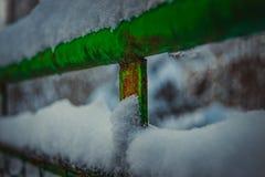 Elemento nevado de la cerca verde vieja imagenes de archivo