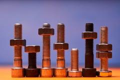 Elementos de conexão na laranja, close-up azul Bolted do fundo fotos de stock royalty free