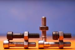 Elementos de conex?o na laranja, close-up azul Bolted do fundo fotografia de stock royalty free