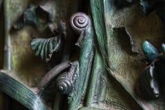 Elementos de los insectos, flores, pájaros de mamíferos en la vieja puerta de la entrada al templo de la familia santa Foto de archivo libre de regalías