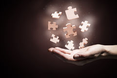 Elementos del rompecabezas en palmas imagen de archivo libre de regalías
