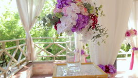 Elementos do projeto de uma cerimônia de casamento Um ramalhete das flores e das orquídeas em um vaso de vidro vídeos de arquivo