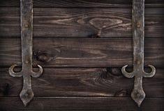 Elementos forjados do metal em portas de madeira escuras Fotografia de Stock Royalty Free