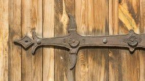 Elementos góticos del hierro labrado en la puerta de madera del tablón Foto de archivo