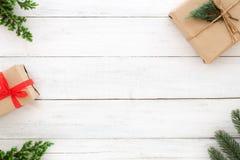 Elementos rústicos de la decoración de las cajas de regalo del regalo de Navidad y de las hojas del abeto en el fondo de madera b imagenes de archivo