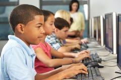 Elementära studenter som arbetar på datorer i klassrum Royaltyfri Fotografi