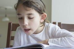 Elementry-Student, der Ihre Hausarbeit liest stockfotografie