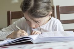 The elementry student is making her homework. She is making her hard homework with most concentrate on book stock photos