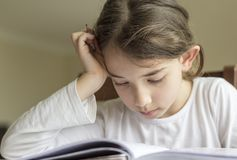 The elementry student is making her homework royalty free stock photo