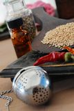 Elements Of Ayurveda. Some of the basic elements of Ayurveda: sesame, chili, tincture, tea ball, and herbs royalty free stock photos