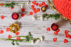 Elements of decor. Red rose petals, candles and flowers on the floor. A lot of red rose petals, red and gold candles in candlesticks Royalty Free Stock Images
