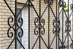 Elements are fragments of a detail of a forged black painted decorative fence made of metal. House fencing, grille, protection,. Security, safety stock images
