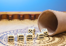 Elements of gambling on a carved wooden board figures six , blue background Royalty Free Stock Image