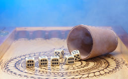 Elements of gambling on a carved wooden board figures six , blue background and smoke Stock Photos