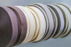 Elements of sewing, textile tapes, rubber bands, rolled up, pastel colors stock photos