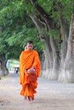Elemosine di camminata di mattina dei giovani monaci asiatici Fotografia Stock