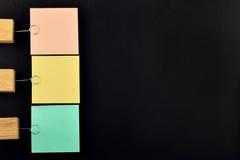 Elenchi, tre note di carta con il supporto sul nero per la presentazione Fotografie Stock