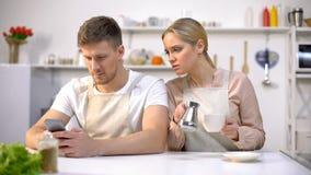 Elende Frau, die am Ehemanntelefon, männliches Simsen mit Liebhaber, Verrat lugt lizenzfreie stockfotos