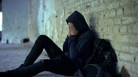Elender Jugendlicher, der im verlassenen Haus, Leben zerstört durch Krieg, Sorge schreit stockfotografie