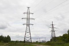 Elenergy pyloner och linjer near storstaden royaltyfri fotografi