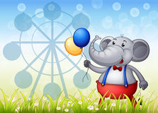 An elephant with balloons in front of the ferris wheel Stock Photos
