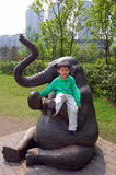 Elephant and boy. A boy sitting on an elephant statue Royalty Free Stock Photo