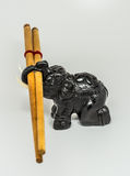 Elephant and Chopsticks. Wooden elephant carrying a pair of chopsticks Royalty Free Stock Photography