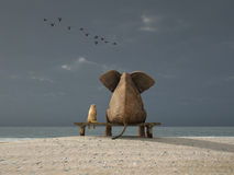 Elephant and dog sit on a beach Royalty Free Stock Image