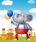 An elephant holding balloons with pots of flower at the back Stock Photos