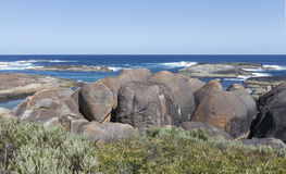 Elephant rocks at williams bay. Three rocks resembling elephants standing next to each other behind green shrubs on the beach. in the background more rocks and stock photography