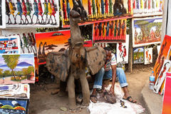 Elephant Statue with Carver and Paintings. A wooden elephant statue with a carver working amongst an African art display Royalty Free Stock Image