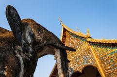 Elephant statue & golden temple. Elephant statue in front of Buddhist temple Wat Chiang Man, Chiang Mai, northern Thailand Royalty Free Stock Photo