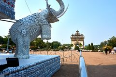 Elephant statue out of cups and plates next to Patuxai Victory Monument The One Attractive Landmark of Vientiane City of Laos stock photos