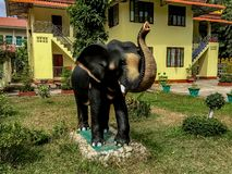 An elephant statue sitting infront of a yellow mortar building w stock photo