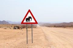 Wild desert elephant warning road sign, Himba people huts, Namibia Stock Photo
