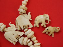Elephants. Four figures from a bone on a red background Stock Photography