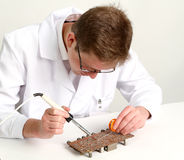 Eletrônica de trabalho que repara a placa que usa a pena de solda imagens de stock
