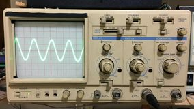Eletr?nica que trabalha com o oscilosc?pio e a onda de seno mostrados no oscilosc?pio video estoque