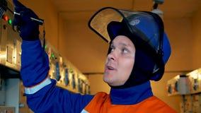 Eletricista com negociações da lanterna elétrica sobre o trabalho da subestação filme