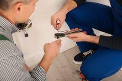 Eletricista e aprendiz que trabalham com fios dentro imagens de stock royalty free
