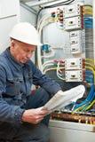 Eletricista em prender com desenhos de funcionamento Fotografia de Stock Royalty Free